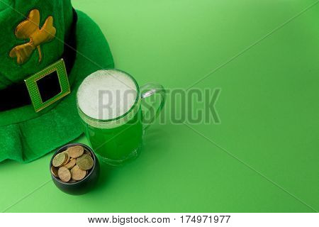 St Patrick's Day green beer with shamrock, horseshoe, pot with coins and Leprechaun hat against green background.