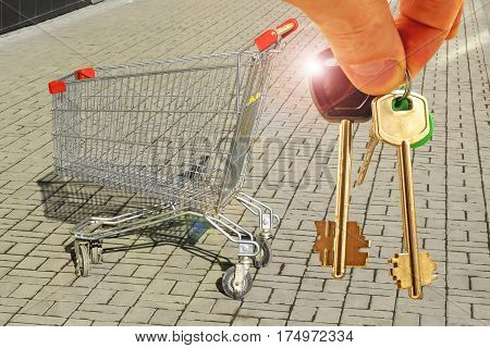 The keys to the apartment in the background of the shopping basket . The concept of development of the real estate market