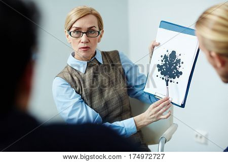Portrait of mature female psychologist wearing glasses showing Rorschach test card to her patient in therapy session