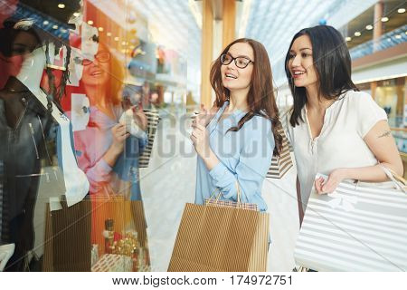 Two girls standing by shop-window at leisure