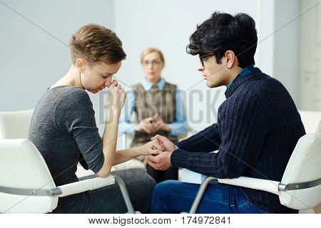 Young couple overcoming problems in counselling, man comforting depressed woman holding her hand