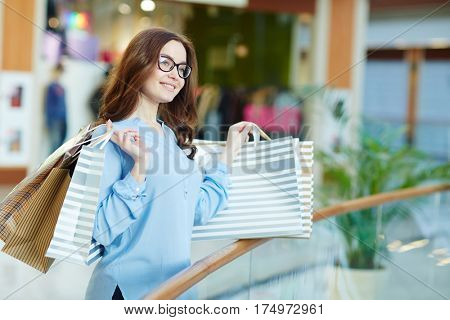Young shopaholic with paperbags enjoying her pastime