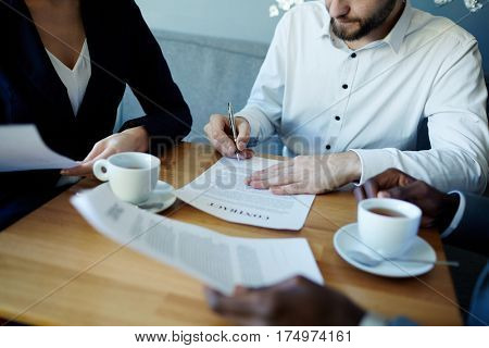 Closeup of three unrecognizable business people sitting at meeting table and sealing deal by signing contract papers