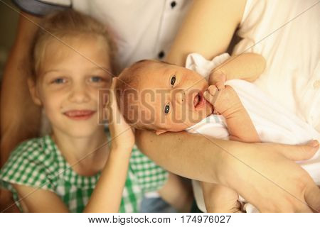 older sister with her newborn sister in the room for children