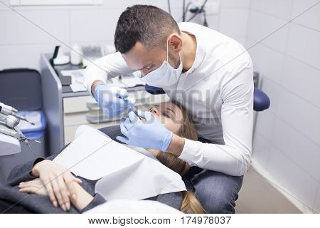 Doctor dentist treats teeth of a beautiful young girl patient. The girl on reception at the dentist. Doctor dentist treats tooth.