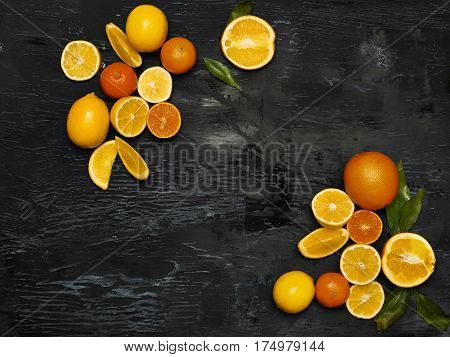 The group of fresh fruits - lemons and mandarins against the black background