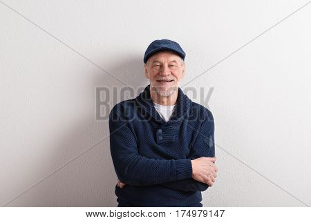 Handsome senior man in blue sweater and flat cap smiling, arms crossed. Studio shot against white wall.