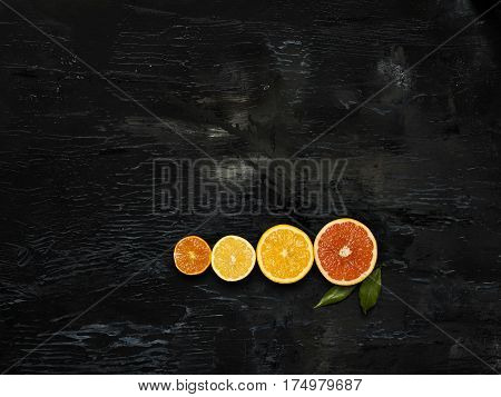 The group of fresh citrus fruits - lemons and mandarins against the black background