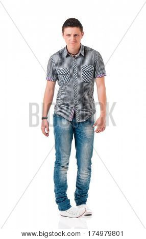 Serious suspicious young man standing, isolated white background. Full length portrait of anger teen boy.