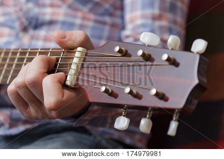 Young Musician Sets Up A Small Guitar. Debugging Musical Instruments