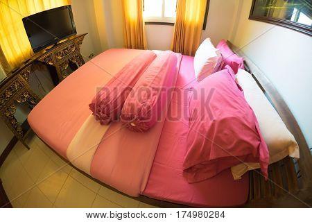 Pink king size bed in apartment, fisheye lane