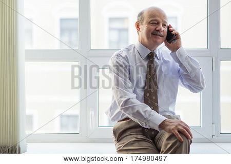 Elderly Businessman Conducts Informal Talks On The Phone