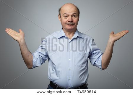 A Man In An Informal Shirt Raises His Arms To The Sides In Bewilderment And Confusion