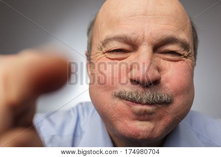 Elderly Man Barely Holding Back Laughter, Puffing Out His Cheeks. Breath Holding