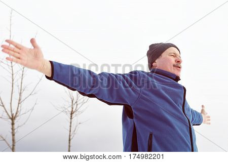 Man in sportswear is engaged in sports and breathes fresh air outdoors