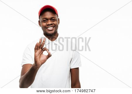 Picture of cheerful young african man wearing cap isolated over white background make okay gesture. Looking at camera.