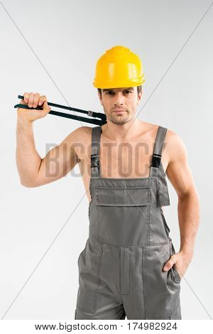 Handsome male builder holding pipe wrench and looking at camera