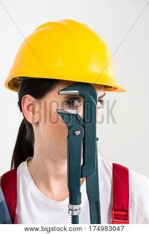 Portrait of female builder holding pipe wrench and looking at camera