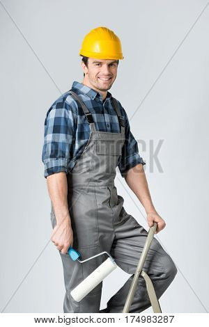 Smiling workman with paint roller standing on ladder