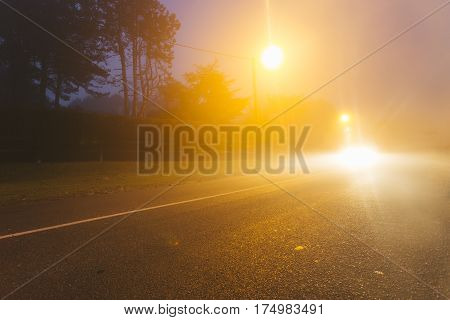 Country Asphalt Road In The Region Of Normandy, France In Foggy Day. Street Lamps And Car Headlights