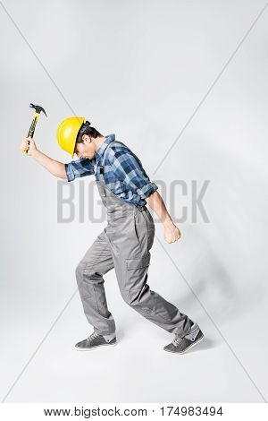 Professional workman in hard hat posing with hammer on grey