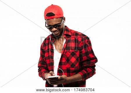 Smiling african young man listening to music and using mobile phone over white background