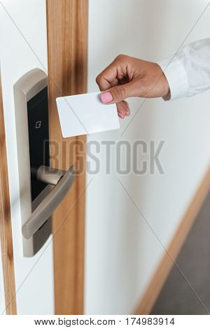 Woman hand inserting key card in electronic lock at hotel