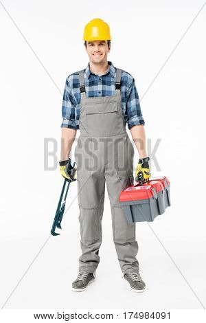 Smiling workman in hard hat holding tool kit and looking at camera on white