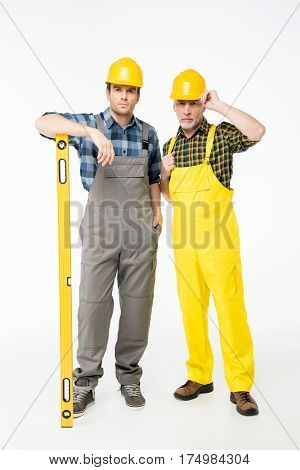 Two workmen in helmets standing with level tool and looking at camera