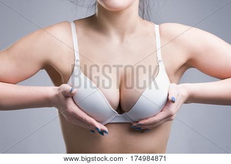 Woman in white push up bra on gray background perfect female breast studio shot