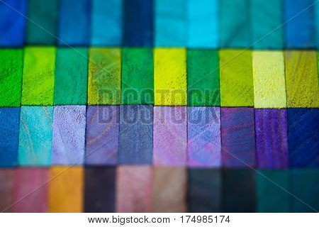 Spectrum of multi colored wooden blocks aligned. Background or cover for something creative or diverse. Extremely shallow depth of field.