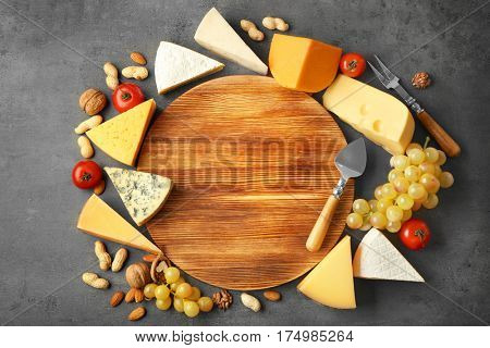 Variety of cheese and nuts around cutting board on dark background