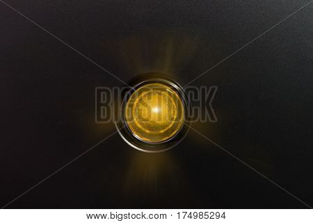 Yellow glowing status indicator, warning lamp or button, on black panel.