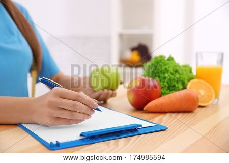 Female nutritionist counting calories in hospital, closeup