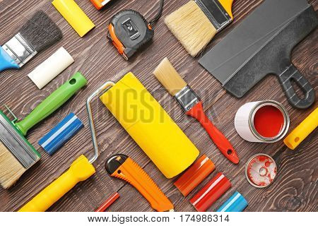 Flat lay composition of decorator and house renovation tools on wooden table