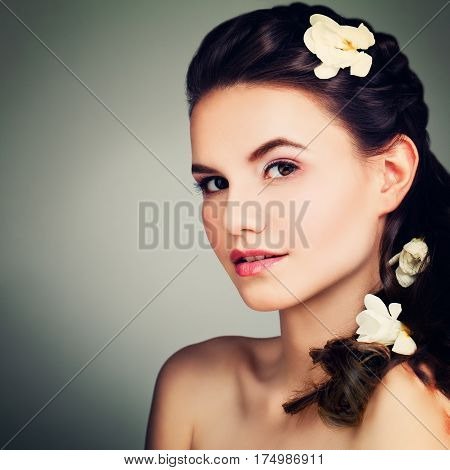 Beauty Portrait of Perfect Brunette Model Woman with Prom Hairstyle Makeup and Flowers at Night