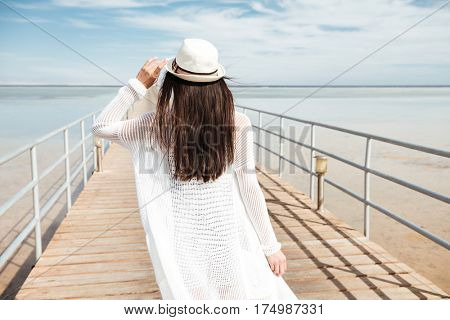 Back view of woman with long dark hair in hat walking on pier