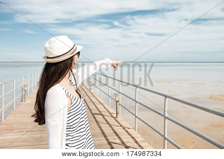Back view of attractive young woman in hat standing on pier and pointing at the sea