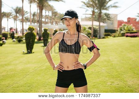 Confident young sportswoman in cap with earphones and armband standing on lawn