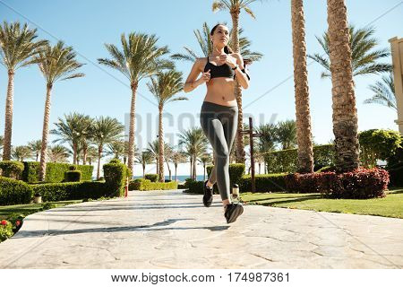 Beautiful young woman athlete running on summer resort in the morning