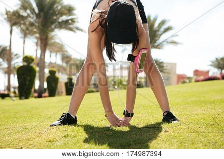 Pretty young fitness woman with blank screen mobile phone in armband working out on lawn