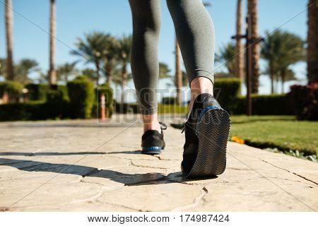 Legs of sportswoman in sneakers and leggings running in summer