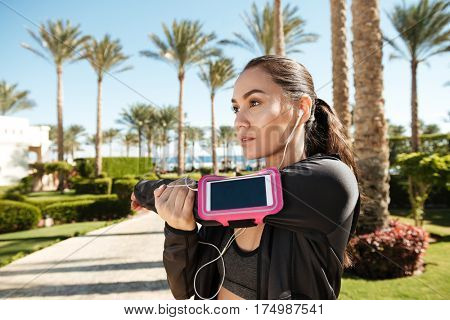 Beautiful young fitness woman with blank screen smartphone in armband stretching arms on summer resort