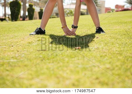 Legs and arms of sportswoman standing and exercising on lawn in summer