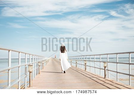 Back view of beautiful young woman in white clothes and hat walking on pier