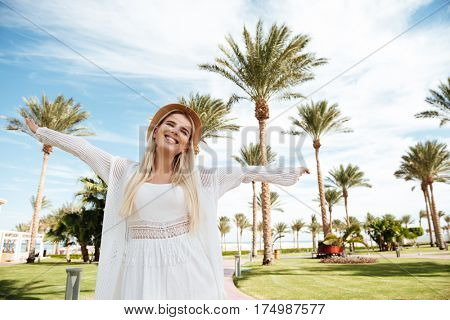 Cheerful carefree young woman in hat standing and having fun on summer resort