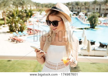 Happy young woman drinking juice and using mobile phone at summer resort