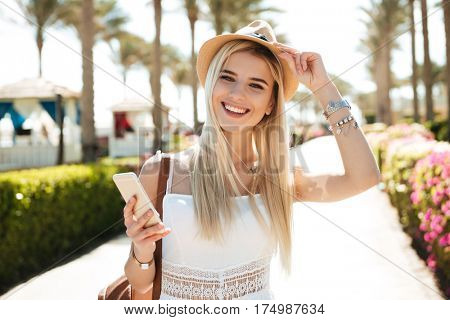Cheerful pretty young woman in hat walking and using cell phone on summer ersort