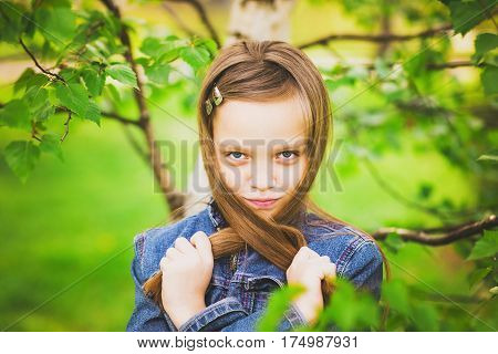 Portrait of spring funny girl. Closeup of beautiful young posing for camera isolated on green grass background. Age of kid is 11 years old.