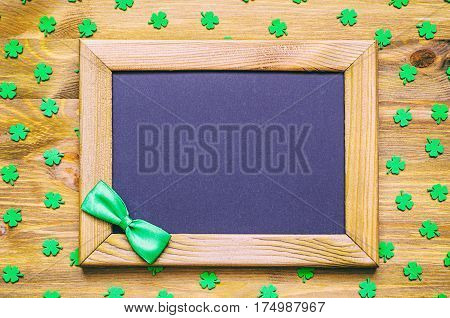 St Patrick's Day background - wooden frame with green bow tie and free space for text and green quatrefoils.St Patrick's Day background -St Patrick's Day is national holiday of Ireland. St Patrick's Day concept. St Patrick's Day background